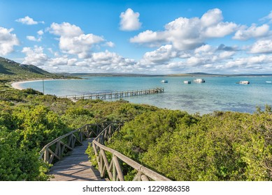 WEST COAST NATIONAL PARK, SOUTH AFRICA, AUGUST 20, 2018: The boardwalk to Kraalbaai at the Langebaan Lagoon on the Atlantic Ocean coast in the Western Cape Province. A jetty and houseboats are visible