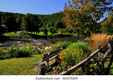 West Cornwall, Connecticut - September 15, 2014:  Wooden park bench with Black-Eyed Susan flowers overlooks the bucolic Housatonic River