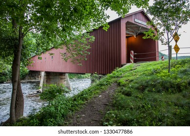 WEST CORNWALL, CT, USA - JULY 15, 2015. The 1864 West Cornwall Covered Bridge. also known as Hart Bridge, is a wooden lattice truss bridge over the Housatonic River.