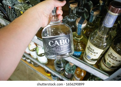 West Covina, California/United States - 02/19/2020: A hand holds a bottle of Cabo Wabo Tequila Blanco on display at a local grocery store.