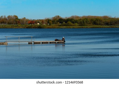West Des Moines, Iowa / US - Oct 16, 2018: An unidentified couple and their dog enjoy autumn weather on a dock on the lake at Raccoon River Park, West Des Moines, Iowa.
