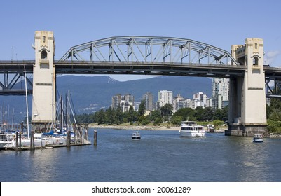 With the West End and the North Shore Mountains in the background, boats of all sizes pass under the Burrard Street Bridge in Vancouver, British Columbia, Canada.
