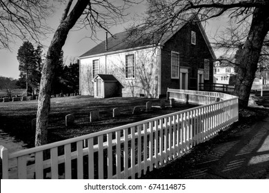West Falmouth MA Quaker Meetinghouse with white picket fence and old colonial cemetery in black and white.