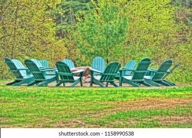 West Greenwich, RI/USA- June 1, 2017: A horizontal high definition image of a dozen green Adirondack chairs arranged in a circle around a fire pit.