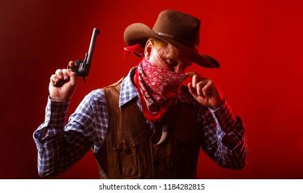 West, guns. American bandit in mask, western man with hat. Portrait of farmer or cowboy in hat. Portrait of a cowboy. American farmer. Portrait of man wearing cowboy hat, gun, macho.