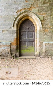 West Haddon, Northamptonshire / UK - June 3rd 2019: Old wooden door, surrounded by carved stone in the stone wall of a church. Two drain covers are in a cobbled stone path.