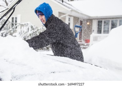WEST HEMPSTEAD,  NY - JAN 3:  Teenager clears snow from his car on Long Island, NY on Jan 3 2014 after snow storm. This powerful nor'easter named Hercules caused blizzard conditions on Long Island.