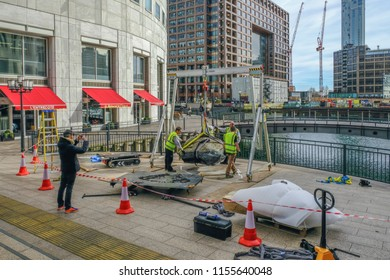 West India Quay, London, UK - March 26, 2017: Workmen in high viz jackets hoisting a large stone beside the water front.  Man taking a photo on his phone.