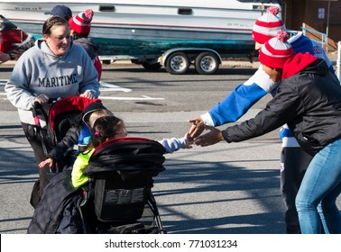 West Islip, NY, USA - 24 November 2017: Even the kids in a stroller get high fives as they get closer to the finish line of the annual Run Your Turkey Off 4K the day after Thanksgiving.