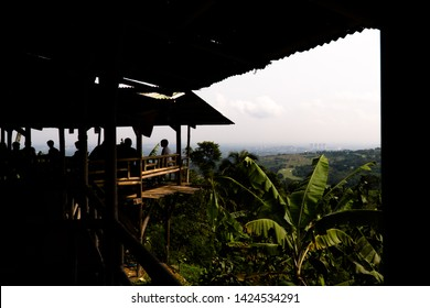 West Java, Indonesia - April 27, 2019: Silhouette of visitors hang out at roadside restaurants in Puncak, Bogor, Indonesia.