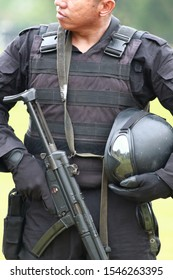West Java/Indonesia - February 26th, 2011: A soldier wearing protection vest and holding his helmet and gun with his face cropped