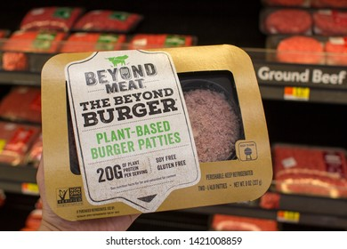 West Linn, Oregon, USA - June 10, 2019: A shopper comparing BEYOND MEAT plant-based burger patties with regular ground beef products at a Walmart supermarket.