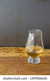 Bo'ness, West Lothian / Scotland - September 7 2019: Glencairn single malt Scotch whisky glass sitting on a wooden board with a rustic metal background