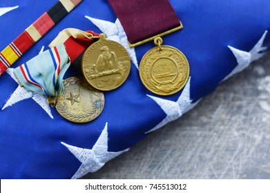 WEST PALM BEACH, FL - October 28, 2017:  Illustrative editorial image of old and worn US Navy service medals laying on a folded American flag. The medals are 1950's vintage from Korean War era.