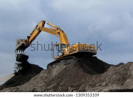 WEST PALM BEACH, FLORIDA - February 10, 2019:A John Deer heavy duty construction shovel moving dirt on an overcast day in West Palm Beach