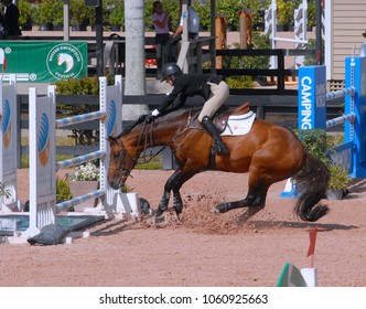 WEST PALM BEACH, FLORIDA - March 30, 2018: Caroline Lynn keeps her seat as her horse balks while competing at week 12 of the Winter Equestrian Festival in Wellington, Florida