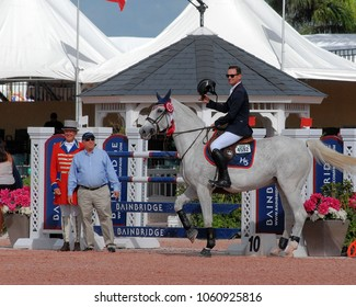 WEST PALM BEACH, FLORIDA - March 30, 2018: Eduardo  Menezes and Caruschka 2 accepting a ribbon at week 12 of the Winter Equestrian Festival in Wellington, Florida