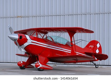 WEST PALM BEACH, FLORIDA - October 17, 2009: A Pitts Special S-2 two-seater aerobatic trainer bi-plane painted in red and white in front of a hangar at North County Airport in South Florida.