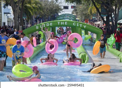 West Palm Beach, Florida, USA - Feb 14, 2015: Slide the City where 1000s of people enjoying a 5 block long water slide is set up on Clematis Street in downtown West Palm Beach, Florida on Feb 14, 2015