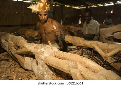 West Papua, Indonesia, Circa May 2011. Asmat tribal men carving totem poles in Omandeseb Village.