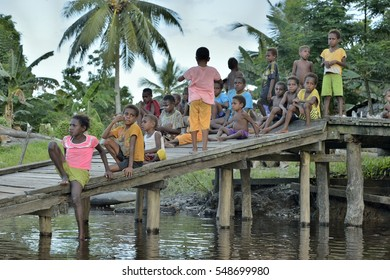 WEST PAPUA (IRIAN JAYA), ASMAT PROVINCE, NEW GUINEA, INDONESIA - MAY 22, 2016: - Children of asmat people sit on wooden bridge on the river. Small village of Asmat in New Guinea jungle. May 22, 2016