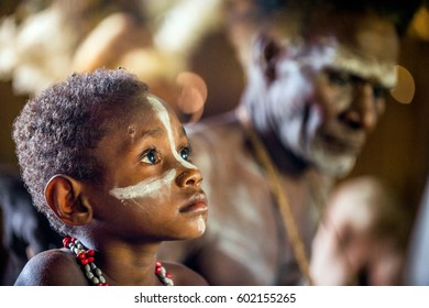 WEST PAPUA (IRIAN JAYA), ASMAT PROVINCE, NEW GUINEA, INDONESIA - MAY 22, 2016: - Unidentified boy of an asmat tribe painting face in a small forest village in jungle of New Guinea. May 22, 2016
