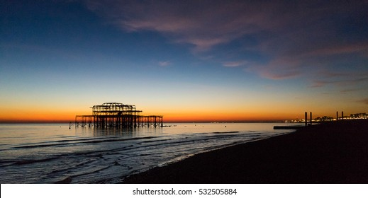 West pier remains at sunset, Brighton and Hove beach, East Sussex, England, United Kingdom
