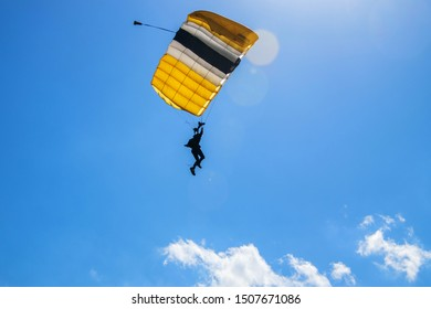 West Point, New York - August 30, 2019: An Army cadet paratrooper was seen gliding through the air with blue skies and clouds in the background