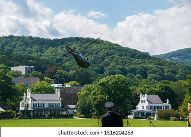 West Point, New York - August 30, 2019: Army military helicopter departs from the parade field with officers watching after bowing to the spectators prior to West Point Military Academy football game