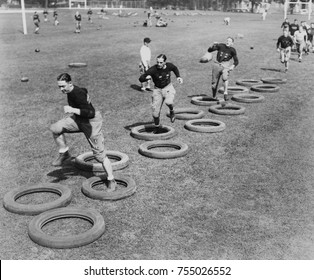 West Point's football squad high stepping through a maze of tires during their first practice. 1920s.