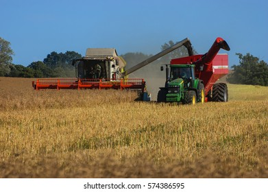 WEST POMERANIAN / POLAND - JULY, 2013: Combine and tractor on the field - harvest rape
