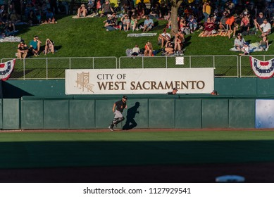 WEST SACRAMENTO, CA/U.S.A. - JUNE 29, 2018: An unidentified Fresno Grizzlie gives a thumbs up as he runs past  the back fence during a game against the River Cats at Raley Field.