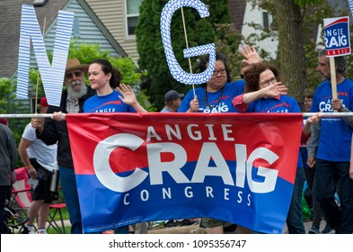 WEST SAINT PAUL, MN/USA – MAY 19, 2018: Supporters of Minnesota congressional candidate Angie Craig march at city festival. Craig is the endorsed candidate of the Democratic-Farmer-Labor Party.