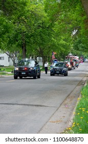 WEST SAINT PAUL, MN/USA – MAY 19, 2018: Parade motorcade fills street of residential neighborhood during annual West Saint Paul Days festival.