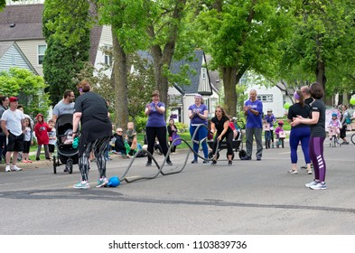 WEST SAINT PAUL, MN/USA – MAY 19, 2018: Woman in the street using battle ropes for fitness training while exercise group members cheer at West Saint Paul Days parade.