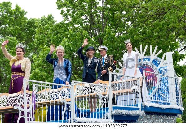 WEST SAINT PAUL, MN/USA – MAY 19, 2018: Saint Paul Winter Carnival royalty waving from parade float at West Saint Paul festival.