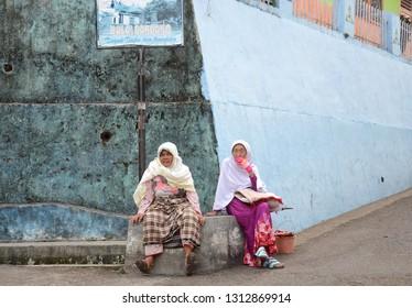 WEST SUMATRA, Indonesia - FEBRUARY 14, 2019 : Two women sitting on the edge of the wall at the Minangkabau village at Tanah Datar, West Sumatra.