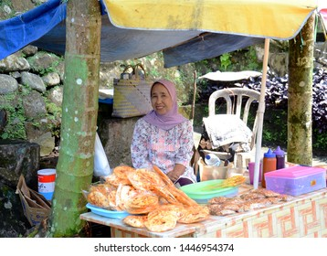 WEST SUMATRA, Indonesia - JULY 10, 2019 : A snack seller waits for customers in front of his shop at Lembah Anai Waterfall, West Sumatra.