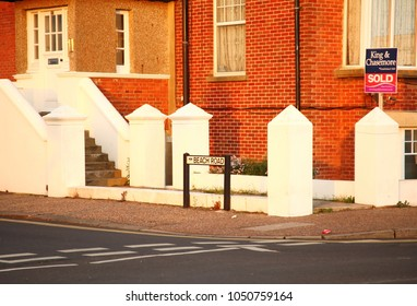 WEST SUSSEX, ENGLAND - NOV, 2: British estate agent signage shown in front of red brick house around beach road represent buy and sell estate business on November 2, 2015 in Littlehampton, England.