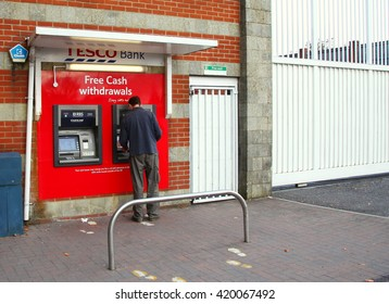 WEST SUSSEX, ENGLAND - OCT, 18: The young man still using the cash machine at retail store background scene on October 18, 2015 in West Sussex England.