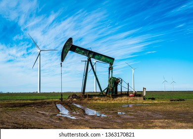 west Texas oil companies using renewable energy to power fossil fuel industry. Oil rig pumping oil in West Texas with huge wind farm creating renewable energy in background. End oil now