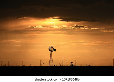 West Texas Sunset. Windmill and pump jack.