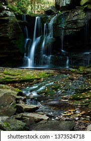 West Virginia Elakala area waterfall deep in the heart of Blackwater State Park. The vibrant green forest of emerald trees creates a tranquil scene. A slow shitter speed captures spiraling, spinning w