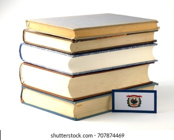 West Virginia flag with pile of books isolated on white background
