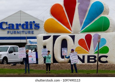 """West Warwick, Rhode Island/USA- May 12, 2018; The """"RI reSisters"""" protest Cardi's Furniture and Speedcraft Auto support of propaganda Trump TV Sinclair Broadcast on NBC WJAR TV 10 on May 12, 2018"""