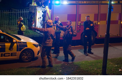 West Yorkshire,United Kingdom - 09/25/20 : UK police officer liasing with the fire brigade at a emergency scene.A police car and a fire engine can be seen.