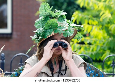Westerbork, Netherlands- July 8, 2018: Young artist with binoculars depicting grumbling during the Championships living statues in Westerbork, the Netherlands