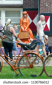 Westerbork, Netherlands- July 8, 2018: young dressed in orange street artist representing the time during the Championships living statues in Westerbork, the Netherlands
