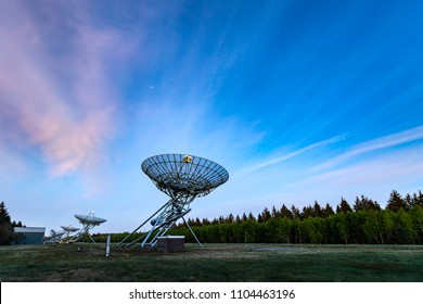 The Westerbork Synthesis Radio Telescope (WSRT) during dusk, with a light cloudy sky and stars a little visible. An aperture synthesis interferometer consisting of a linear array of 14 antennas.