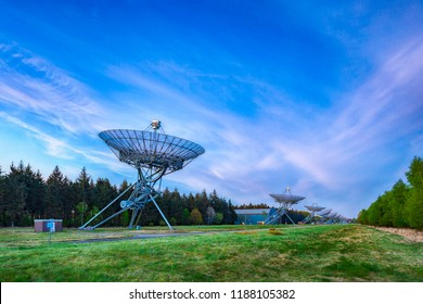 The Westerbork Synthesis Radio Telescope WSRT during dusk, with a light cloudy sky and stars a little visible. An aperture synthesis interferometer consisting of a linear array of 14 antennas.